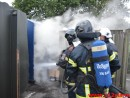 Brand i tøj container.
